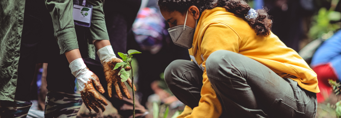 Girl wearing mask planting a tree