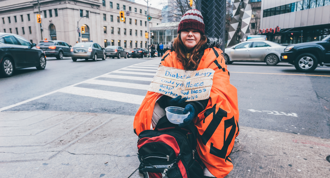 Homeless person on street corner wearing a hat and holding a sign