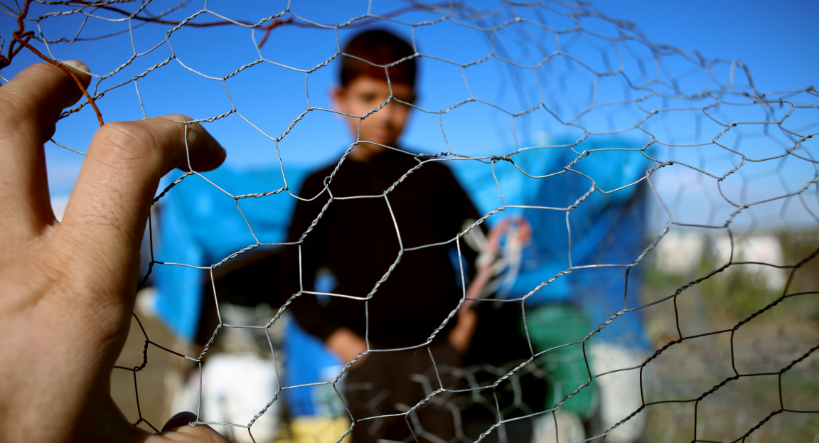 Boy at refugee camp looking through fence